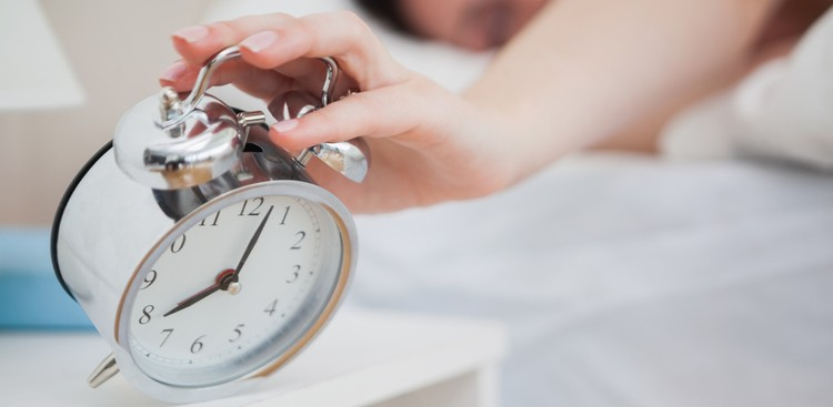 woman hitting alarm clock