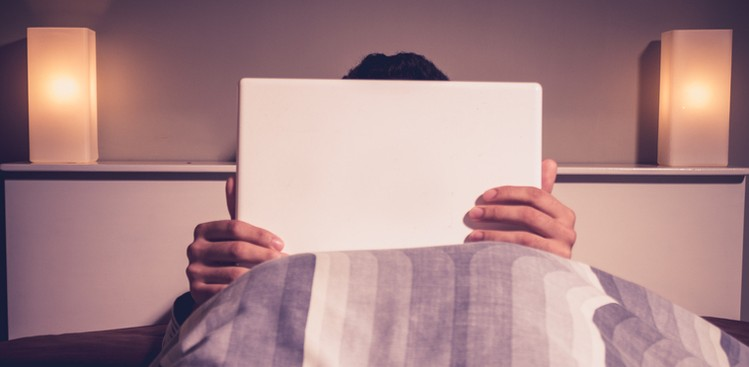 man using laptop in bed