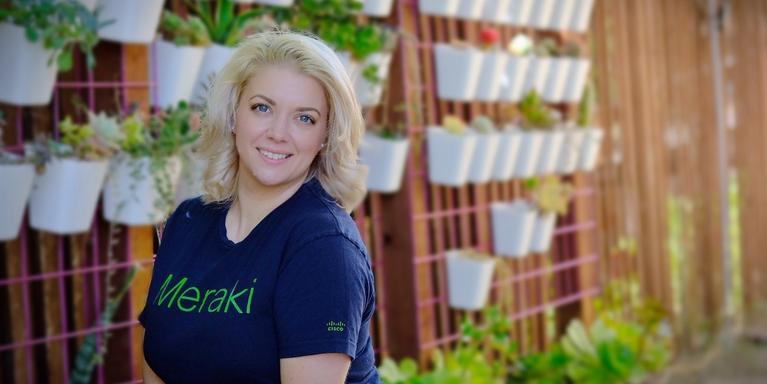person with short blonde hair standing next to a wall of plants