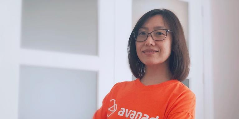 a person with shoulder-length hair and glasses wearing an orange T-shirt