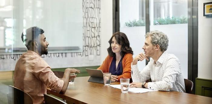 three people sitting at a conference table talking