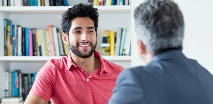two people talking at table in front of book case