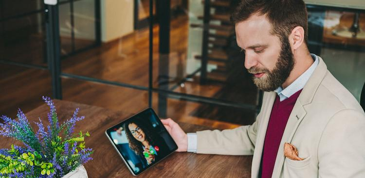 person sitting at a table making a video call on a tablet