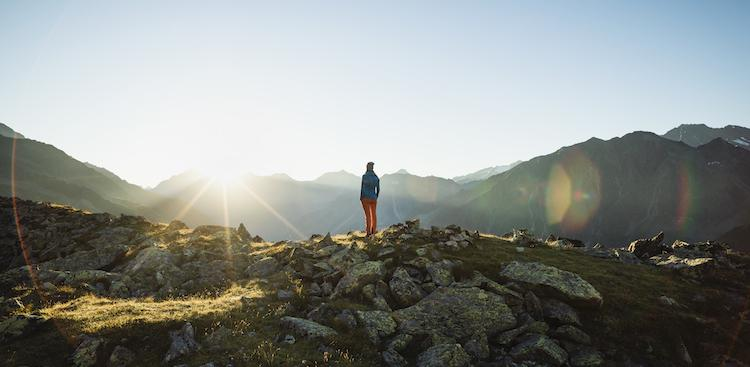 person looking at the sunrise in the mountains