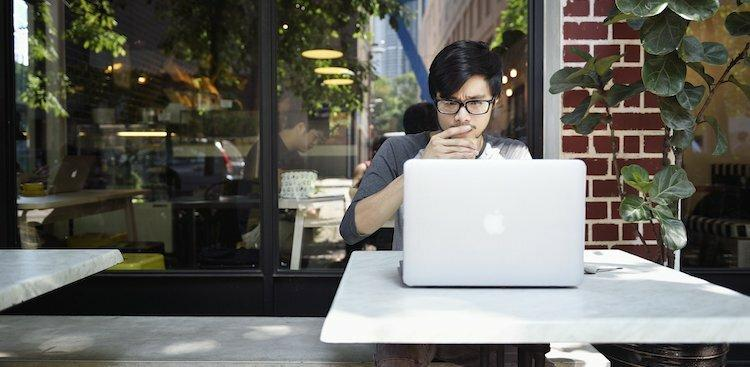 person sitting at an outdoor table working on a laptop