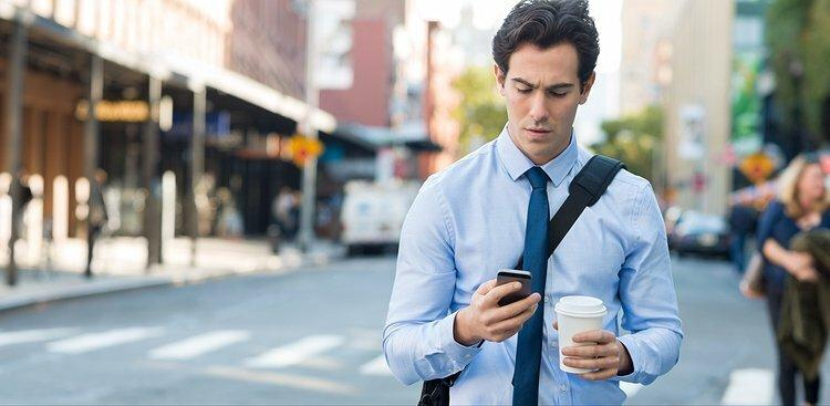 man checking email on way to work