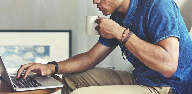 man with coffee on laptop