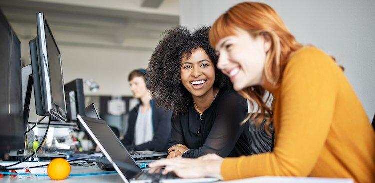 two women smiling and working at computers