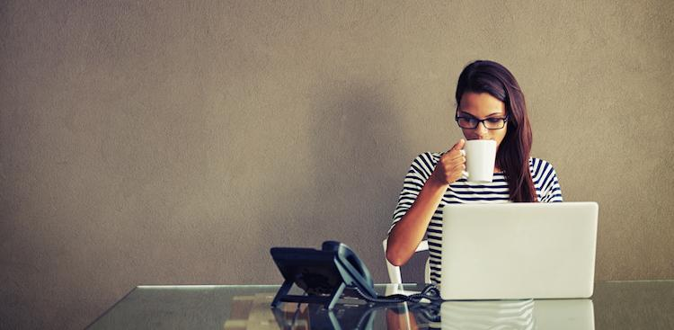 person drinking coffee at laptop