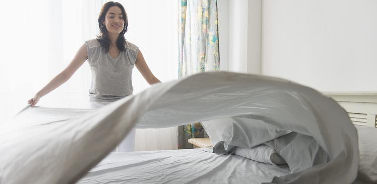 person making bed