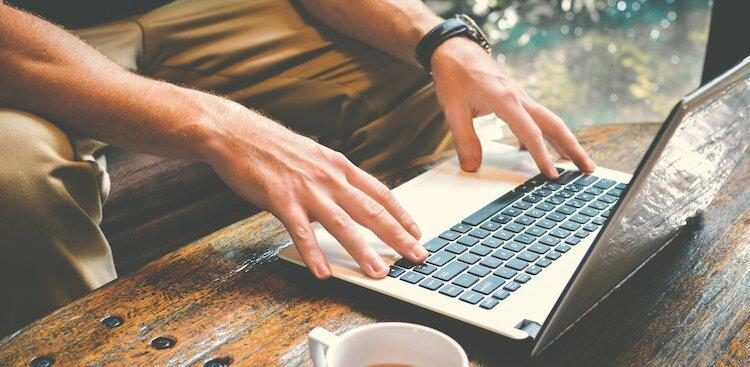 hands of person on laptop