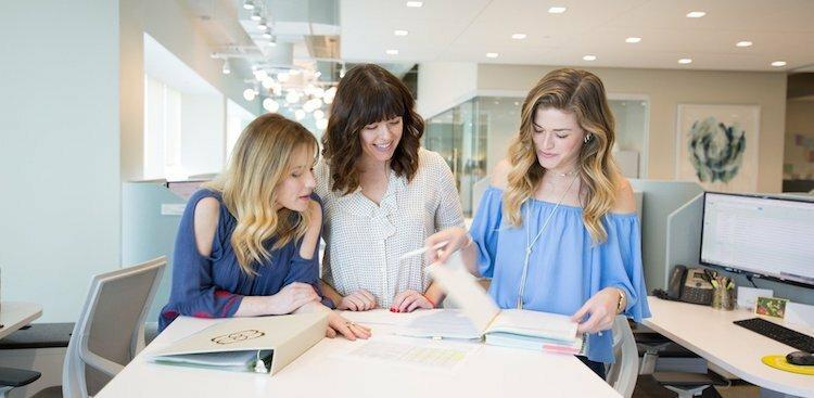 three Kendra Scott employees browsing through project notes
