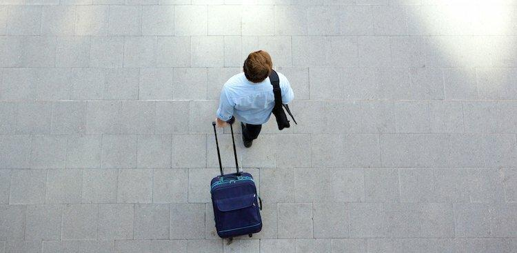 person walking with suitcase