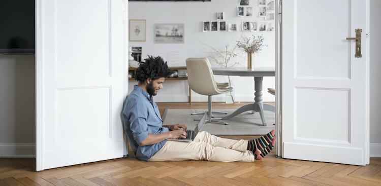 person on laptop on floor