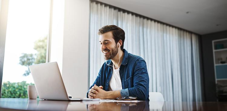 person smiling at computer and wearing headphones