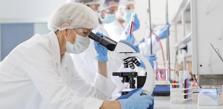 Scientists wearing protective gear looking through microscope