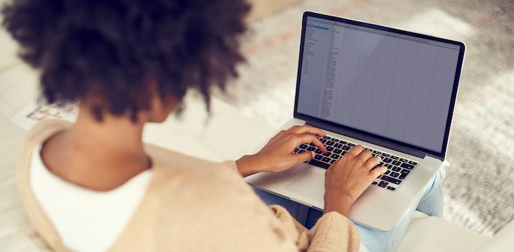 person sitting on couch typing on laptop viewed from behind