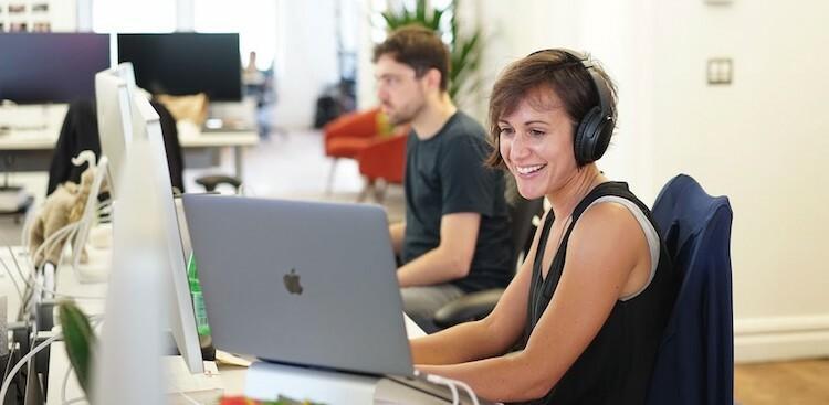 an employee wearing headphones working at Asana's New York City office