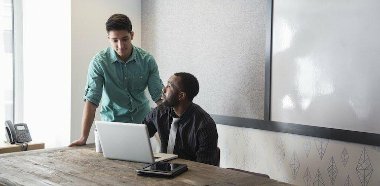 two people sitting at office table with laptop