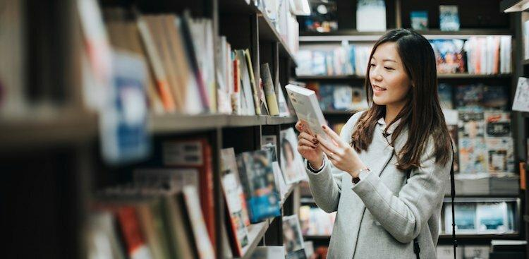 person looking at book in bookstore