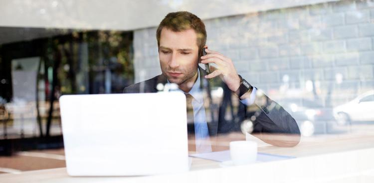 person on the phone looking at computer