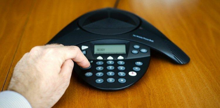 person's hand dialing a phone
