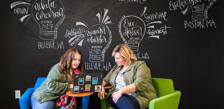 two Smartsheet employees working on a laptop