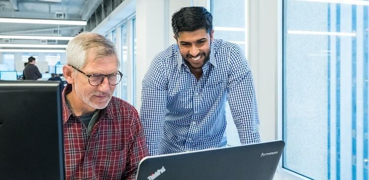 two Klaviyo employees working on a laptop