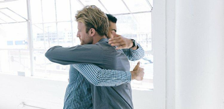 people hugging in office
