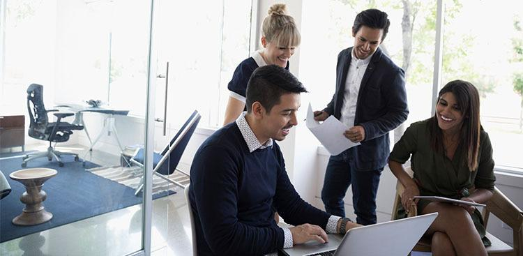 group of colleagues working together with a laptop