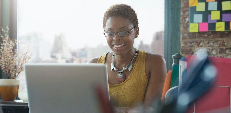smiling person working on laptop