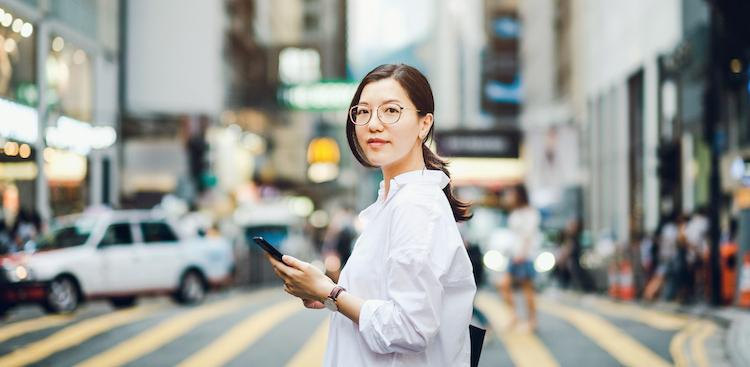 person using phone on a city street