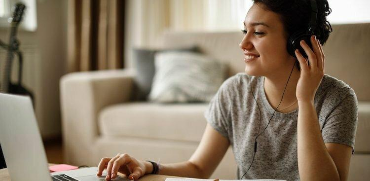 person sitting on floor with laptop on coffee table