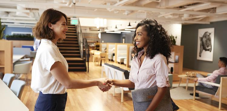 two people shaking hands in an open office