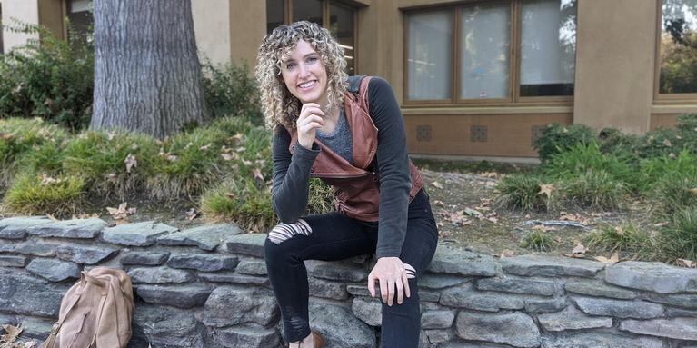 smiling person with curly hair sitting on a stone wall