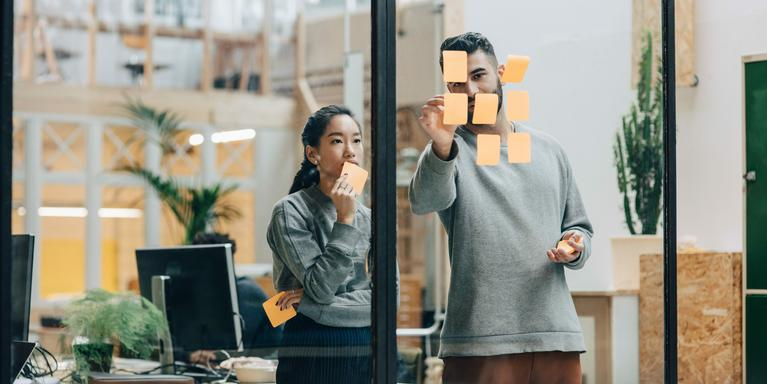 two people discussing while sticking adhesive notes on glass wall in office