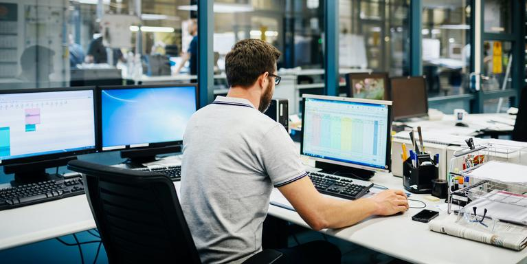 person at desk looking at spreadsheet