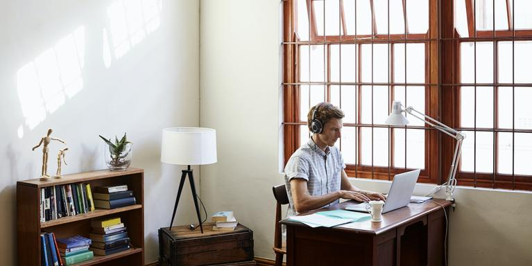 Person on laptop in home office with headphones on