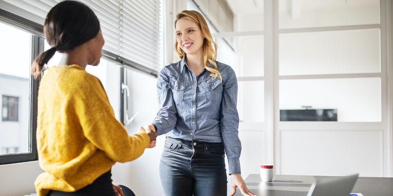 two people shaking hands in conference room before interview