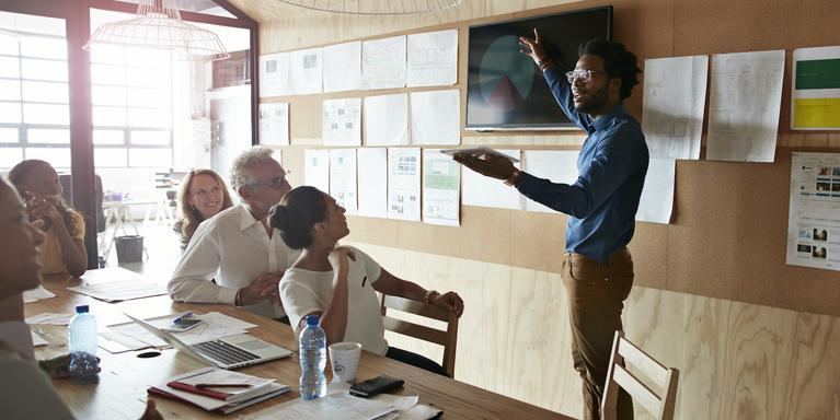 person giving presentation in conference room to group of people