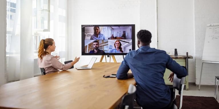 two people in conference room on video call with rest of their team