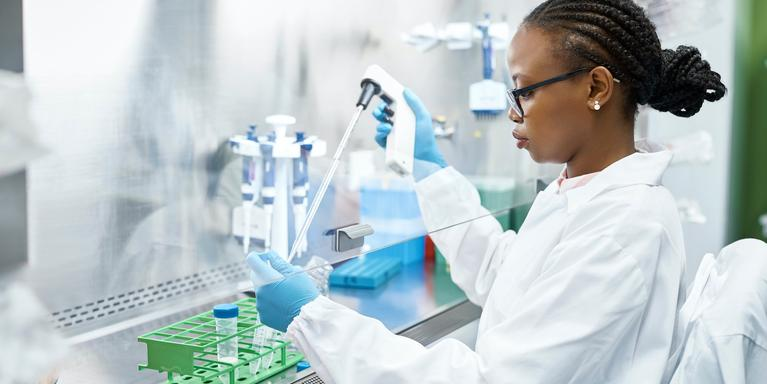 person pipetting under a laboratory hood