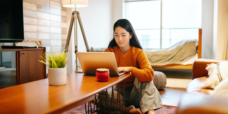 person sitting on floor with laptop on coffeetable