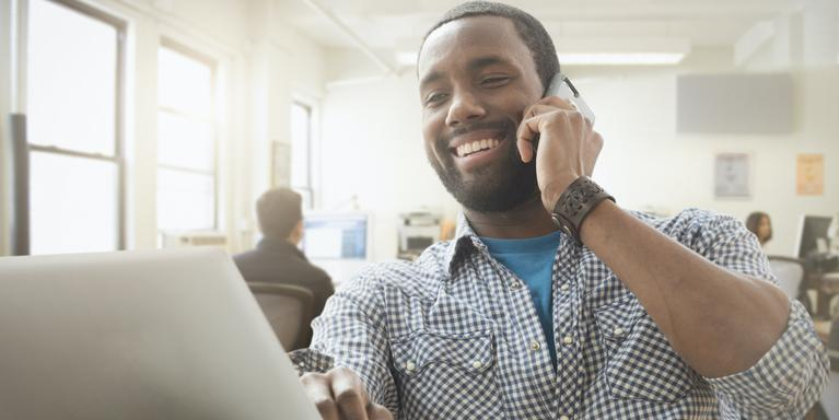 person in open office talking on phone while looking at laptop