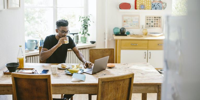 person drinking juice and working from dining room table