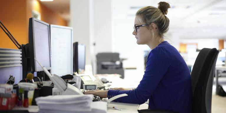 person sitting at desk with double computer monitors in office
