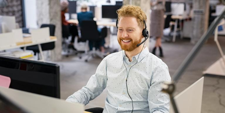 person sitting at desk in office with phone headset on