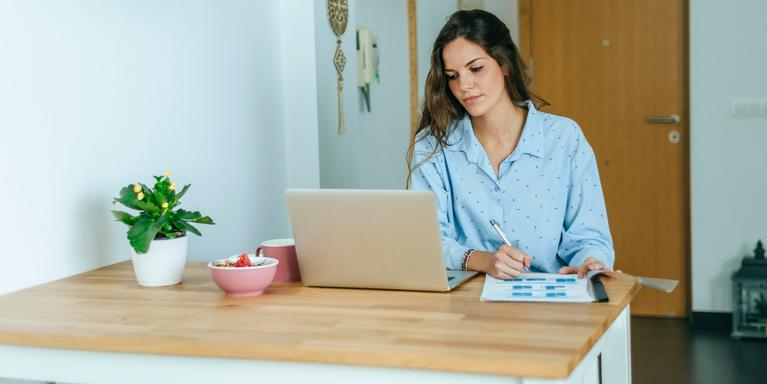 person sitting at kitchen table on laptop while writing something on paper
