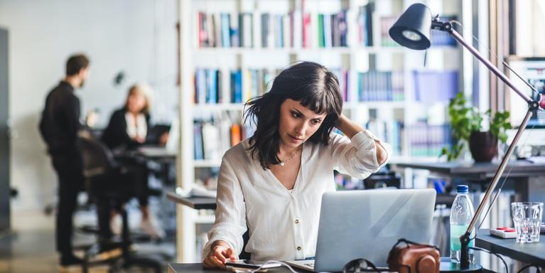 person working at laptop in office with out-of-focus coworkers in the background