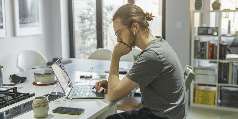 person sitting at kitchen counter with laptop wearing AirPods with phone next to them